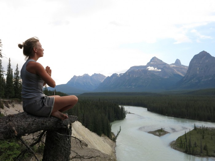 Finding inner peace in the lotus position in the nature with a beautiful Rocky Mountains lake view