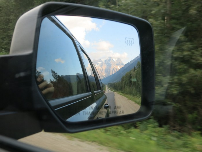 Car's side mirror shows the Rocky Mountain scenery