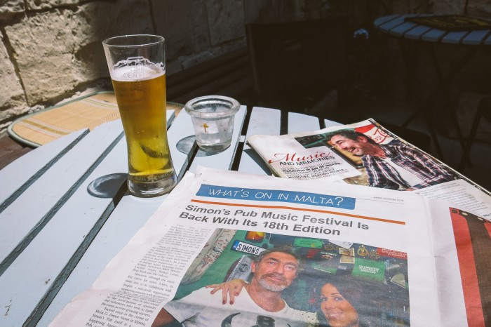 I was basking outside in the sun, drinking cold Cisk and reading articles about Simon