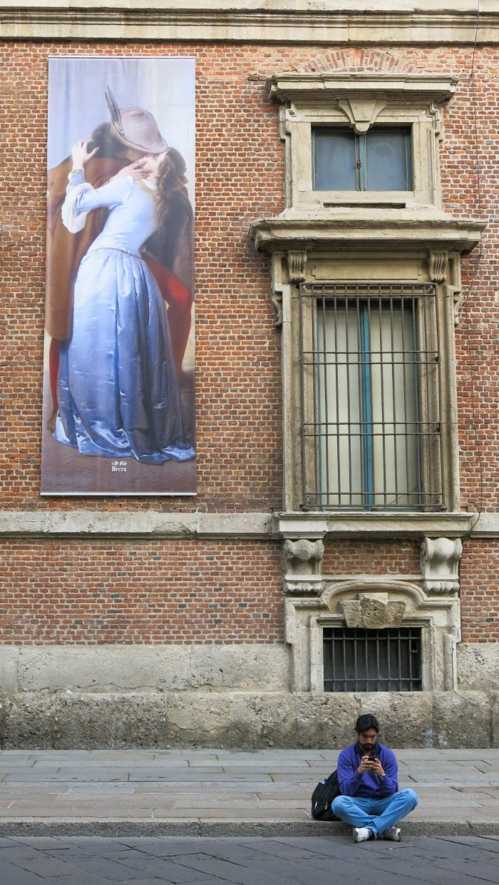 A man texting his girl in front of Milan Art School